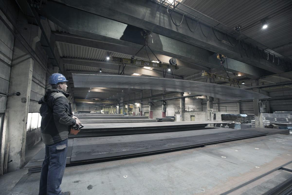 Ein Arbeiter hebt Stahlplatten mit einem Lastkran